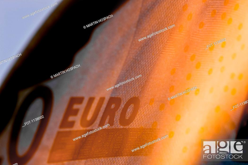 Stock Photo: A twenty euro banknote on fire, extreme close up.
