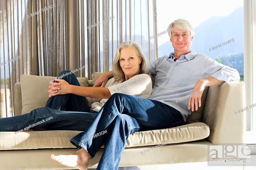 Stock Photo: Middle aged couple reclining on couch.