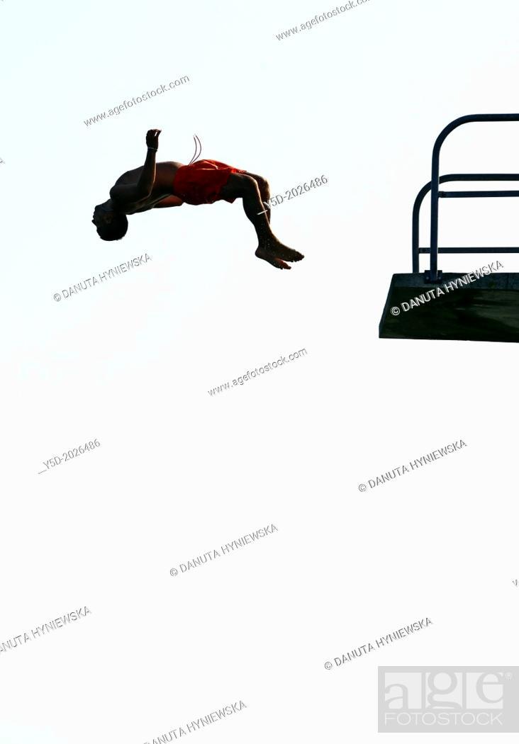 Stock Photo: single man jumping from diving tower to waters of Lake Geneva, head first, Paquis beach, Geneva, Switzerland.