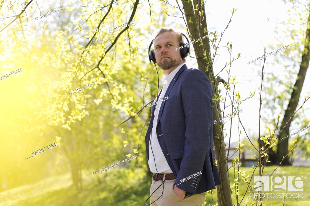 Stock Photo: Male entrepreneur listening music while looking away at park on sunny day.
