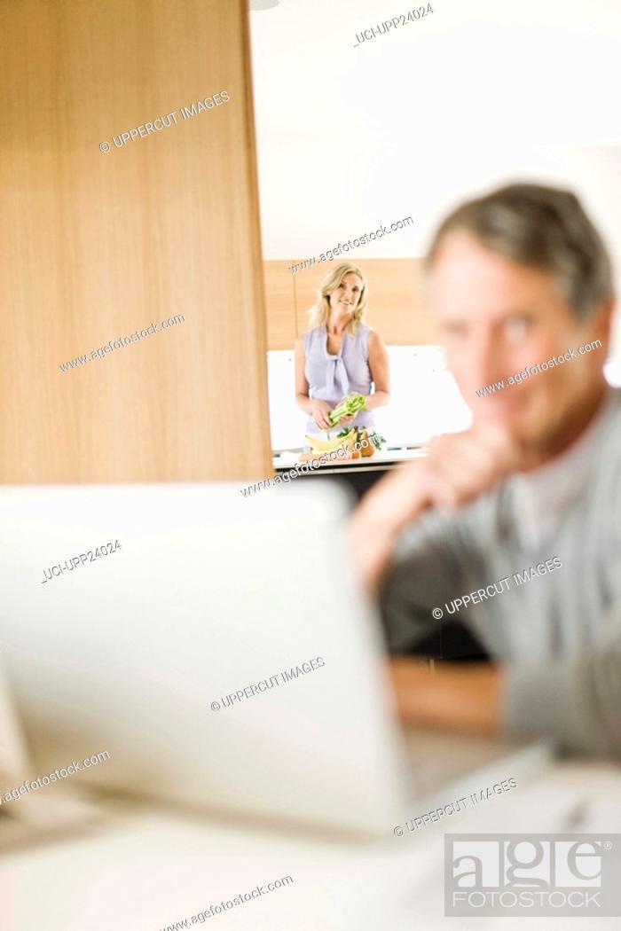 Stock Photo: Woman in kitchen watching husband using laptop,.