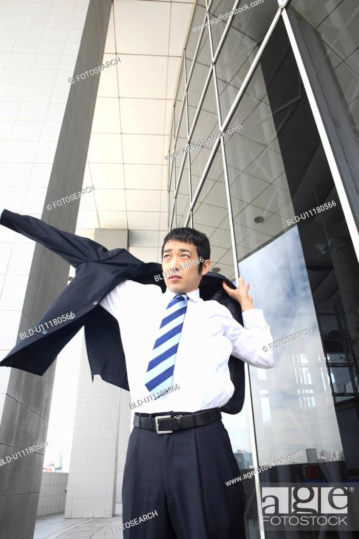 Stock Photo: Businessman putting on a suit.