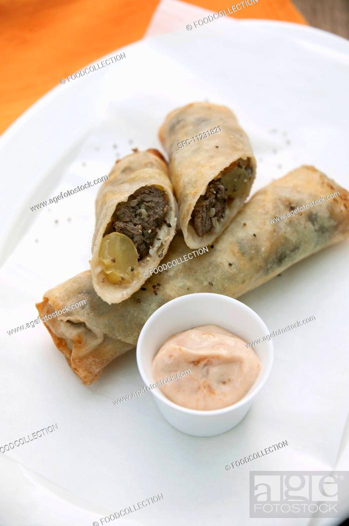 Stock Photo: Small spring rolls with grapes and venison.