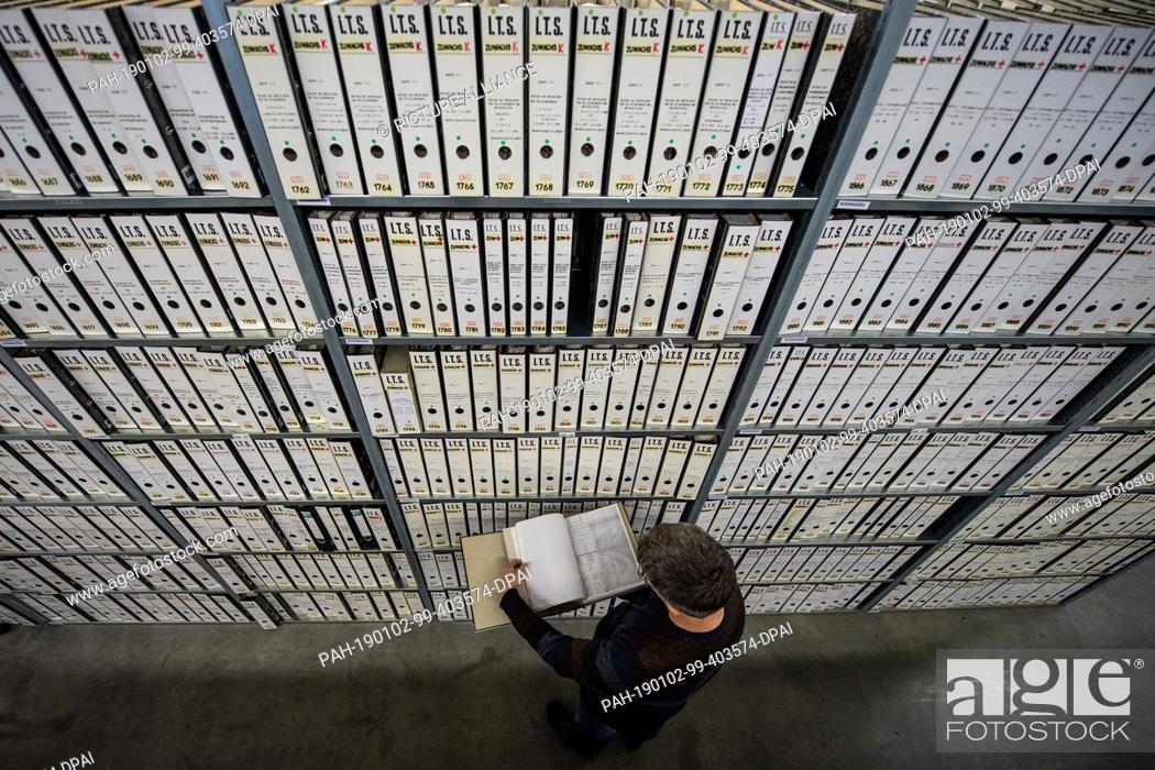 Stock Photo: 11 December 2018, Hessen, Bad Arolsen: Christian Groh, Head of the Archive Department, leafs through a file at a filing cabinet in the provisional archive of.