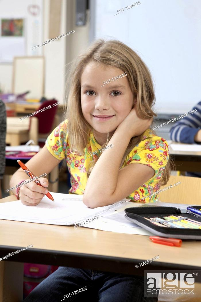 Stock Photo: Girl with book in classroom, portrait.
