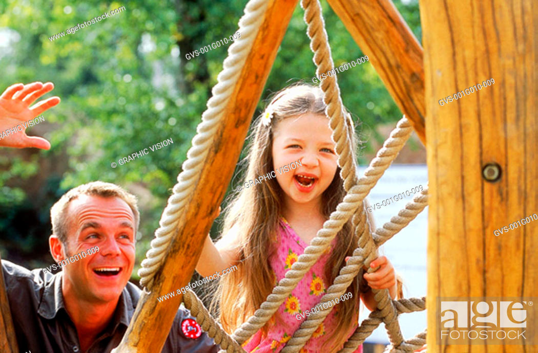Stock Photo: Father and daughter playing on a jungle gym.