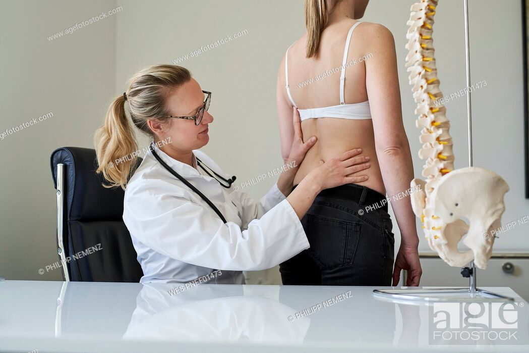 Stock Photo: Female doctor examining back of patient in medical practice.