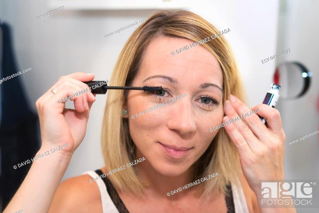 Stock Photo: Beautiful blonde woman applying mascara on her eyelashes.