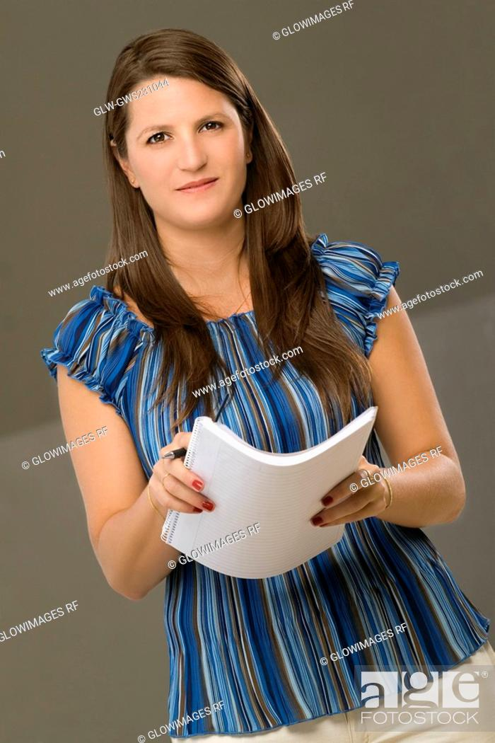 Stock Photo: Portrait of a mid adult woman holding a spiral notebook.