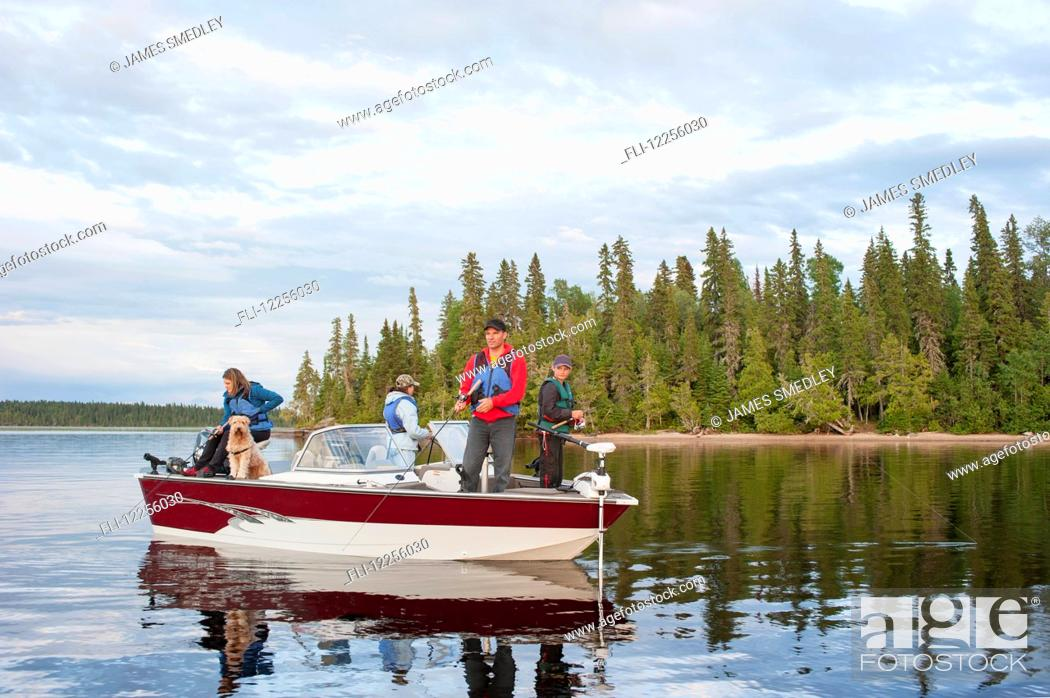 Imagen: A family fishing from their motorboat on a calm lake in Northern Ontario; Ontario, Canada.
