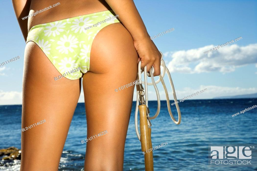 Stock Photo: Close up of derriere of a young adult female holding jump rope in swimsuit on beach.