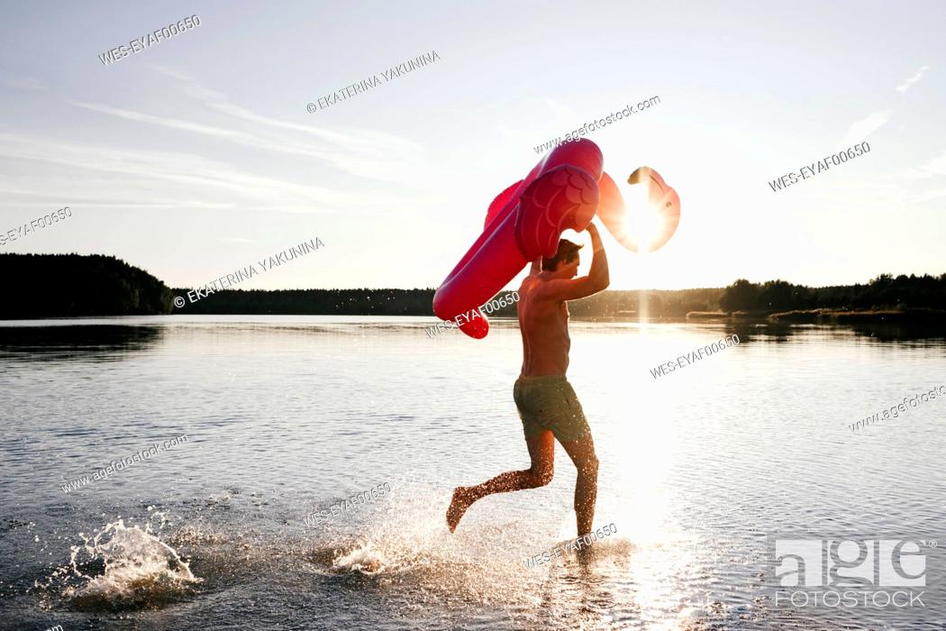 Stock Photo: Young man running with flamingo pool float into a lake.