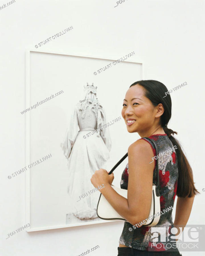 Stock Photo: Woman in art gallery, turning to one side, smiling.