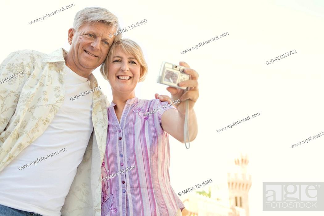 Stock Photo: Man and woman with digital camera taking self-portrait.