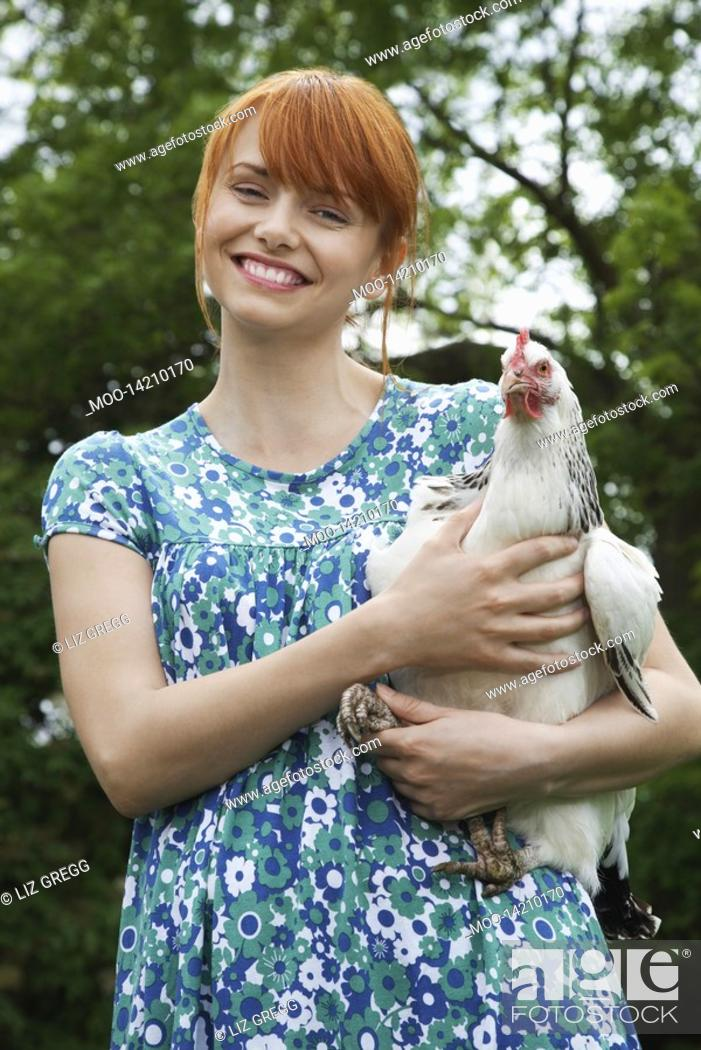Stock Photo: Woman holding hen in garden portrait.