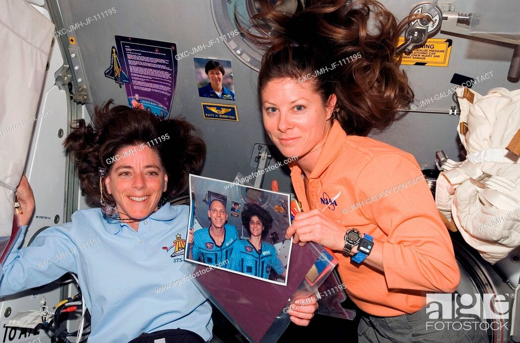 Stock Photo: Astronauts Barbara R. Morgan (left) and Tracy Caldwell, both STS-118 mission specialists, pose with a photo of astronauts Clay Anderson and Sunita Williams.