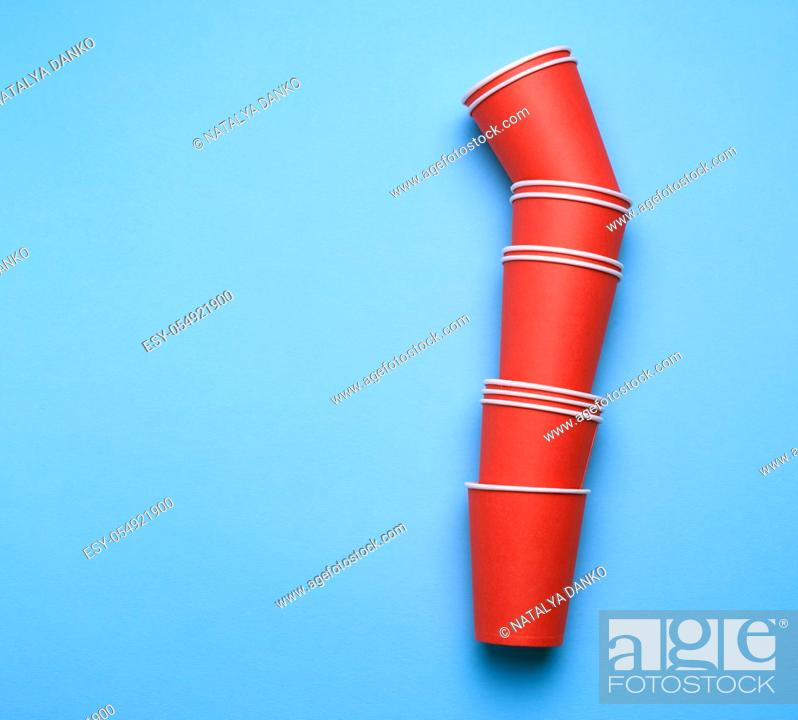 Stock Photo: stack of red paper disposable cups on a blue background, flat lay, concept eco-friendly, zero waste.