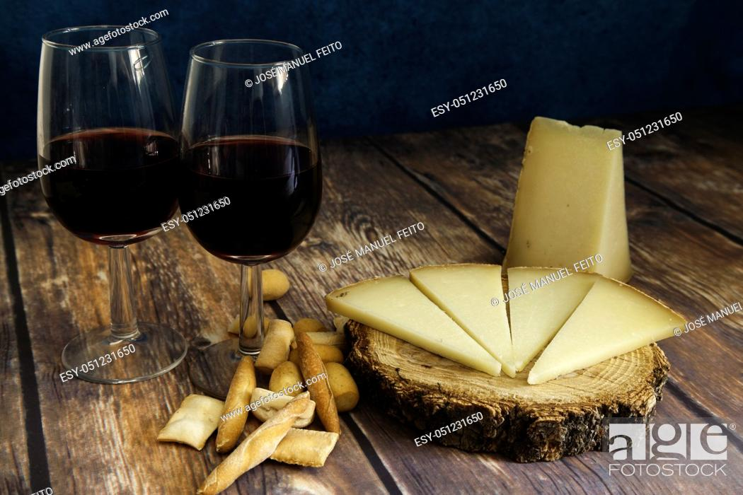Stock Photo: piece and slices of typical Spanish Manchego cheese on wood slice with peaks of bread, two glasses of red wine and napkin on wood table and blue background.