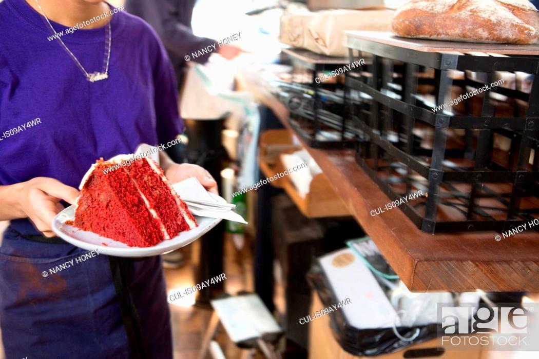 Stock Photo: Waitress serving red velvet cake in cafe.