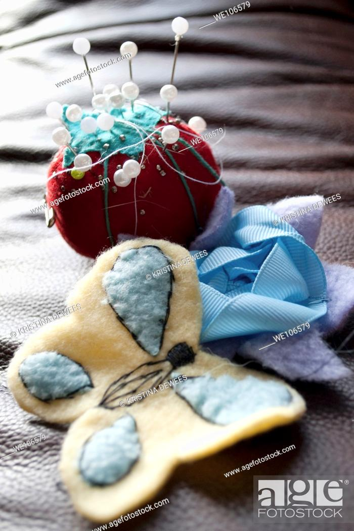 Stock Photo: A tomato pin cushion and a flower and butterfly sewn by hand.