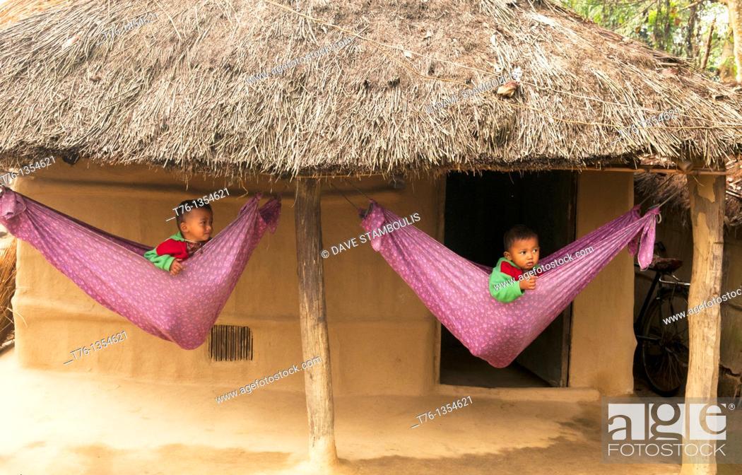 Stock Photo: cute boys in hammocks in a Tharu village in Chitwan National Park in Nepal.