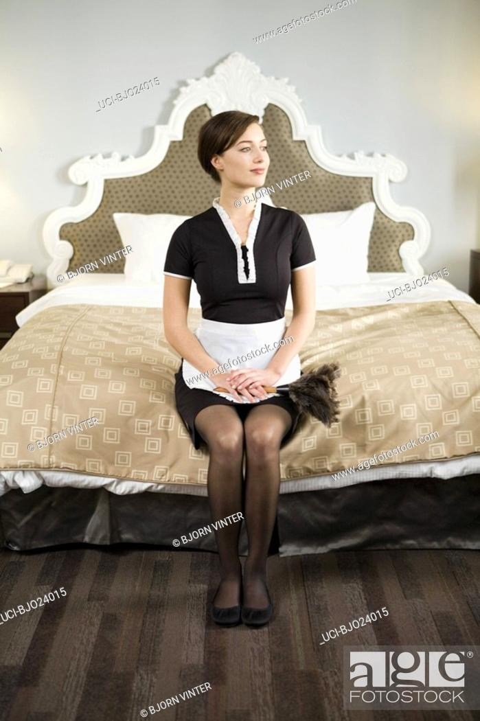 Stock Photo: Maid sitting on edge of bed.