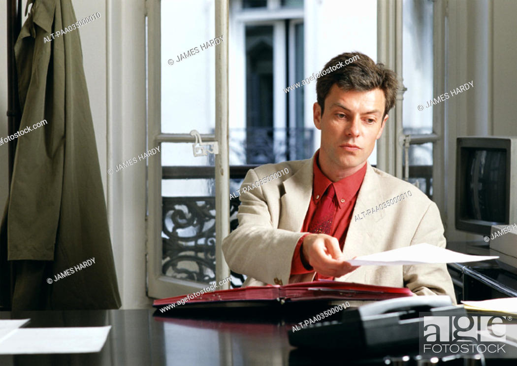 Stock Photo: Man sitting at desk, holding paper.