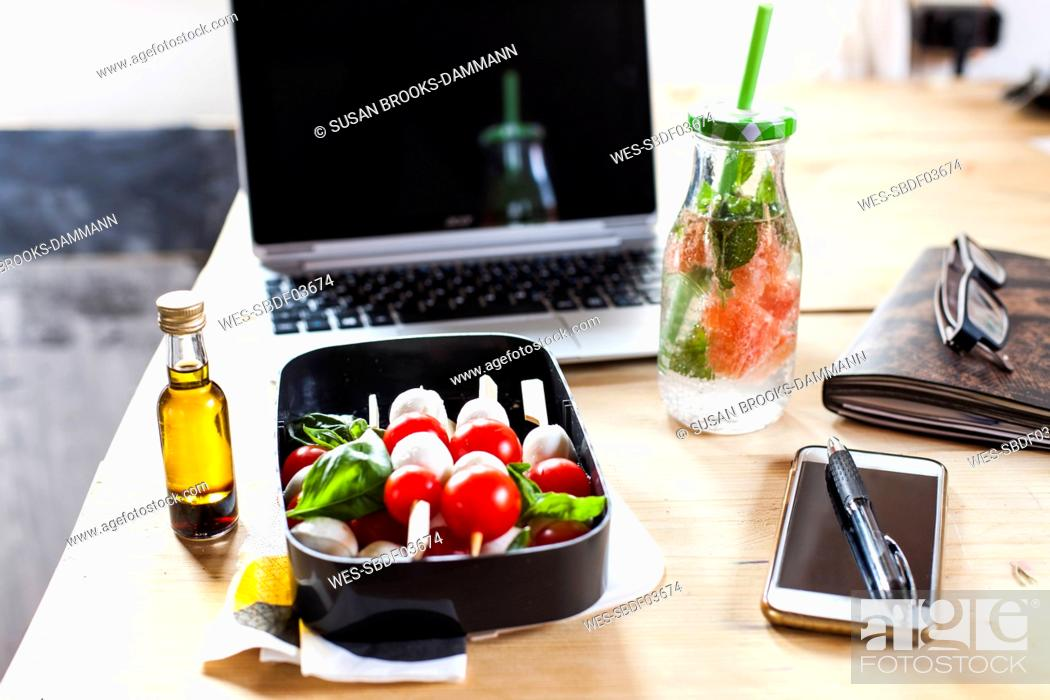 Stock Photo: Lunch box of Caprese salad, bottle of infused water and laptop on desk.