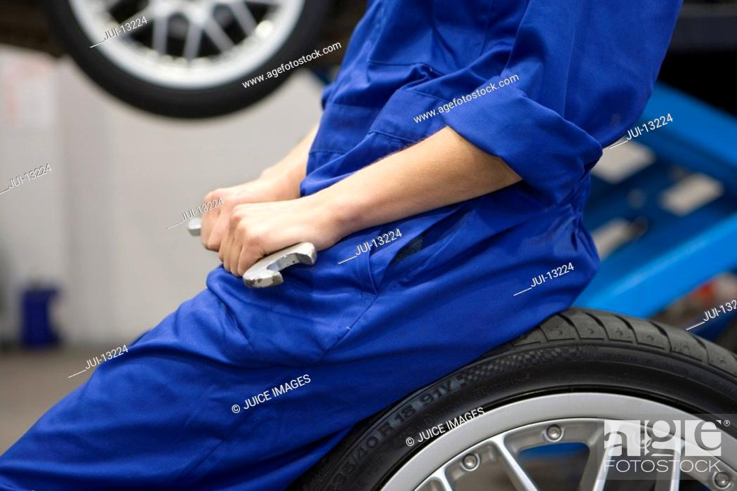 Stock Photo: Female mechanic with wrench on tyre by elevated car, mid section.