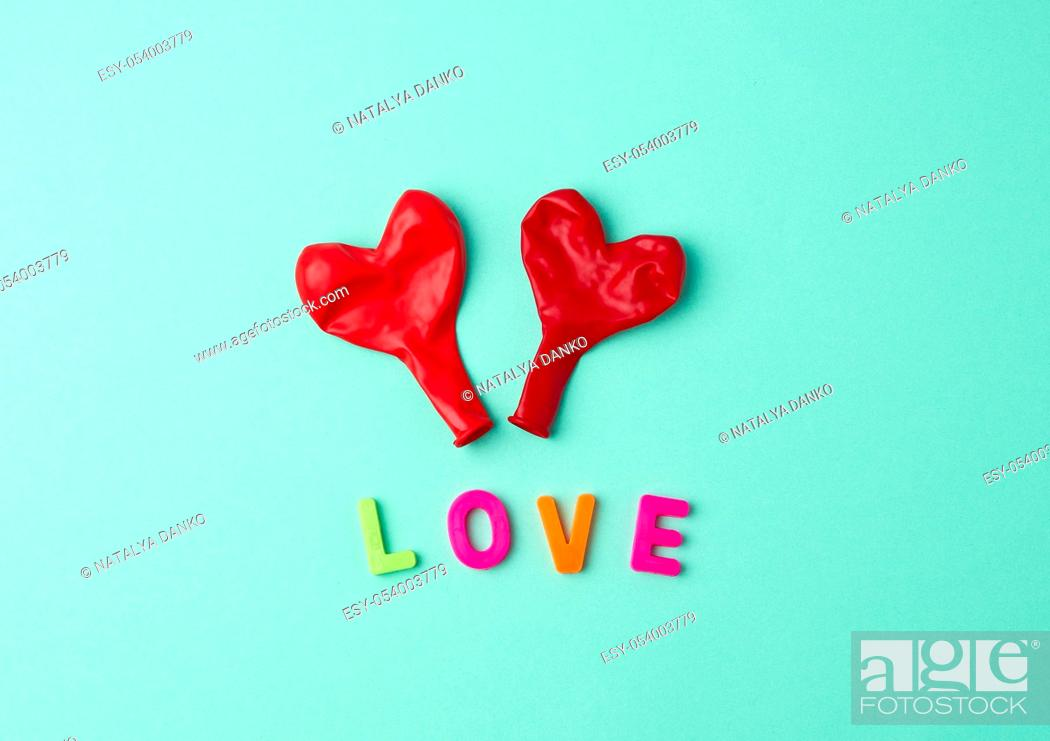 Stock Photo: two red rubber balloons blow away in the shape of a heart on a green background.