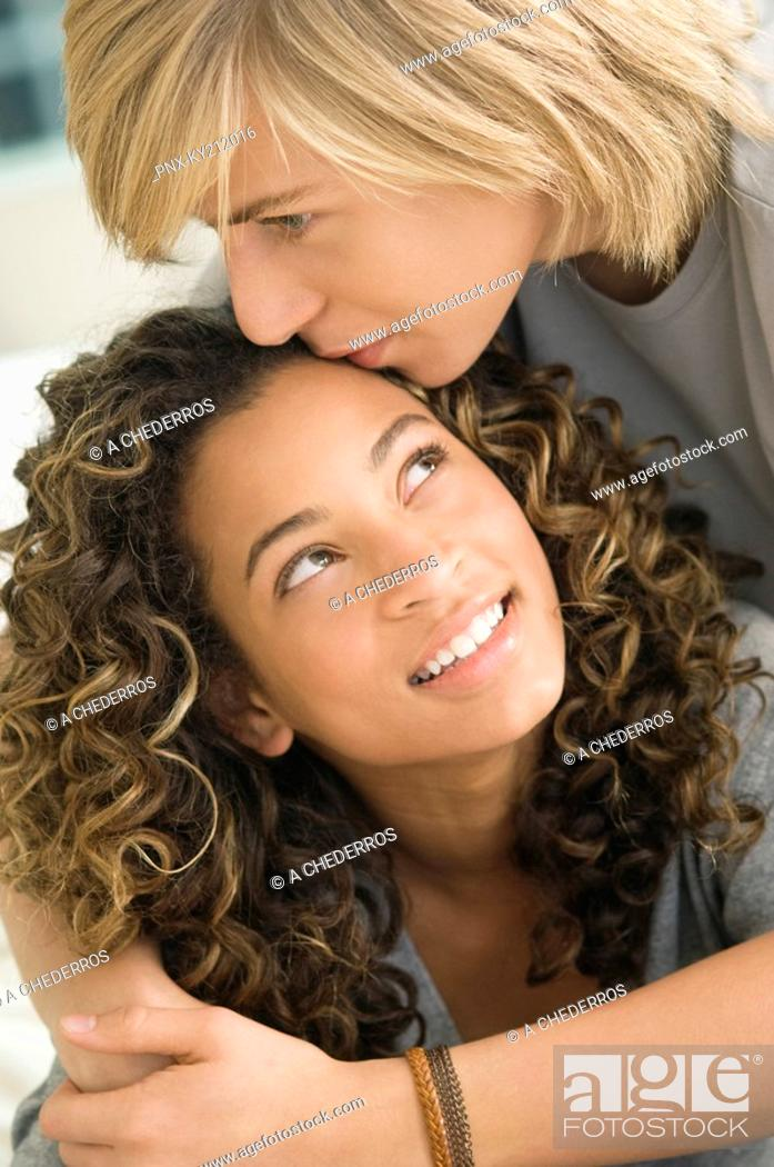 Stock Photo: Teenage boy kissing on the forehead of a girl.