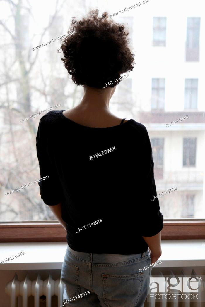 Stock Photo: Rear view of a woman looking through a window.