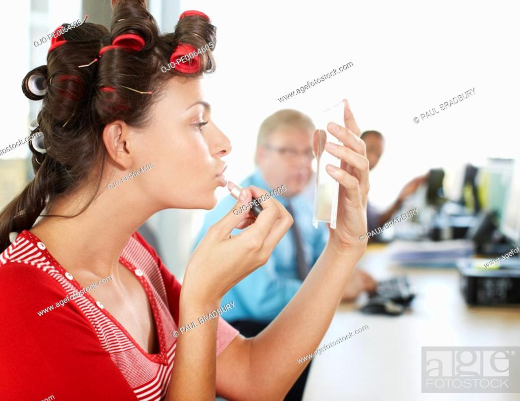 Stock Photo: Businesswoman in curlers applying lipstick at desk.