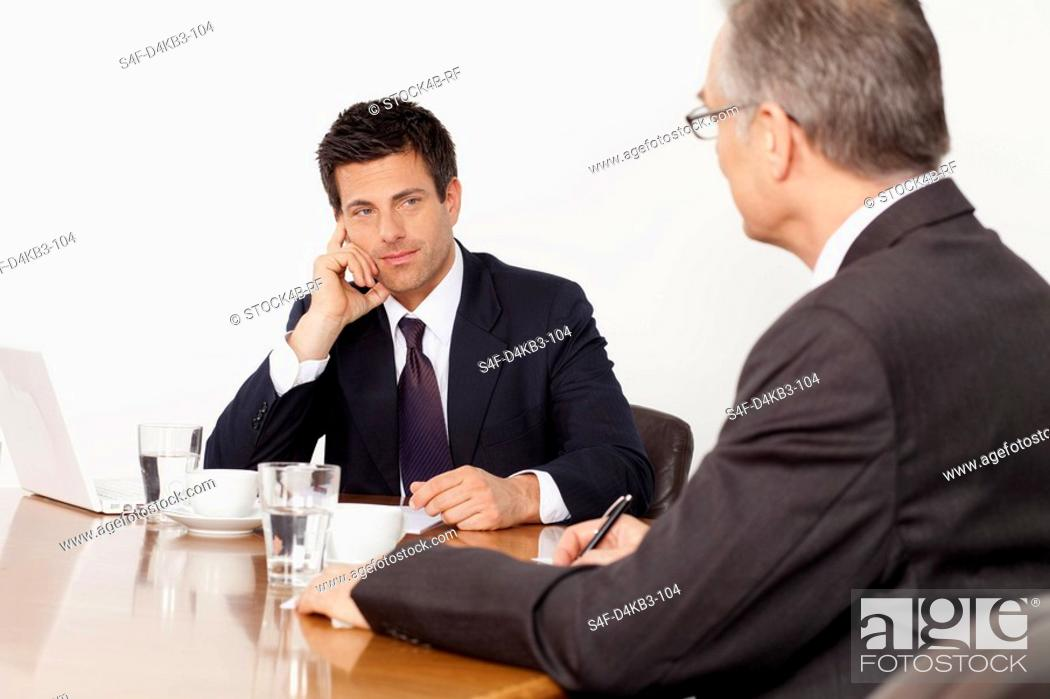 Stock Photo: Two businessmen talking in conference room, Munich, Bavaria, Germany.