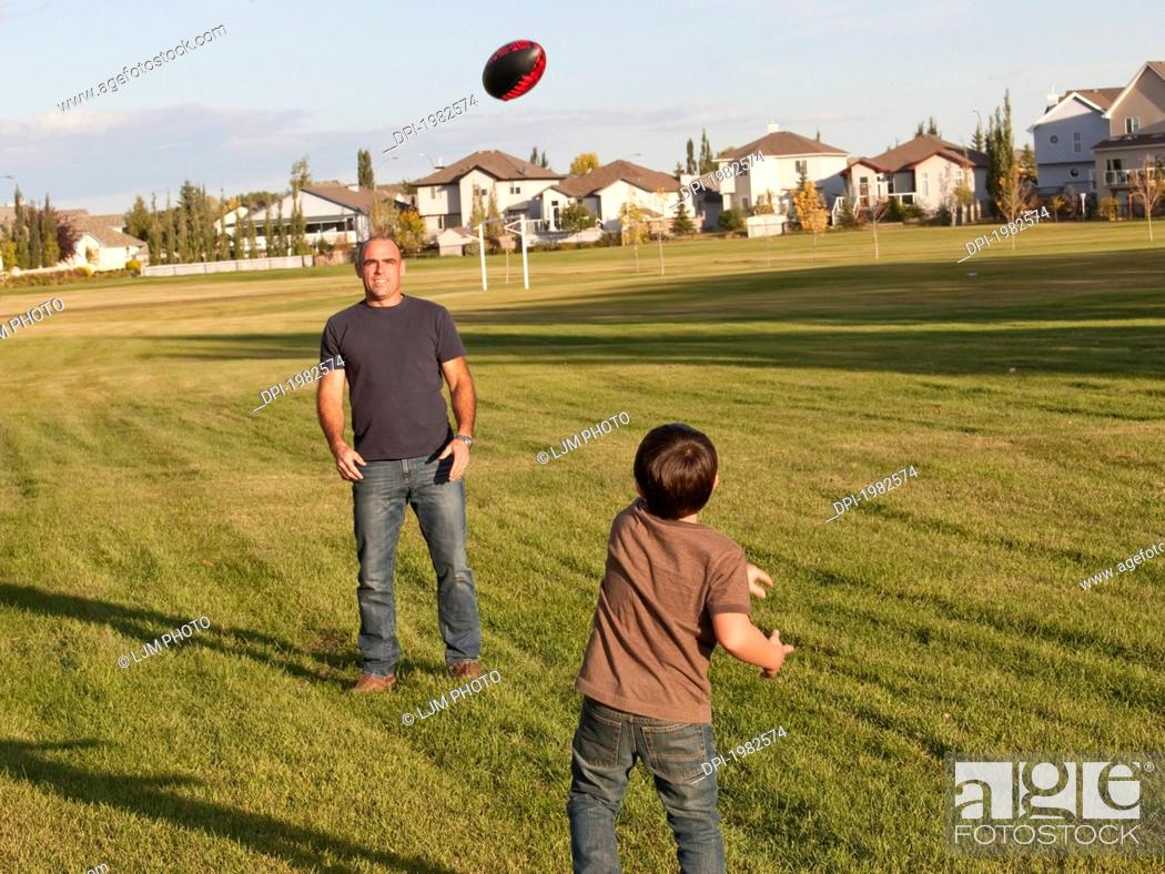 Stock Photo: father and son playing football in a park, beaumont alberta canada.