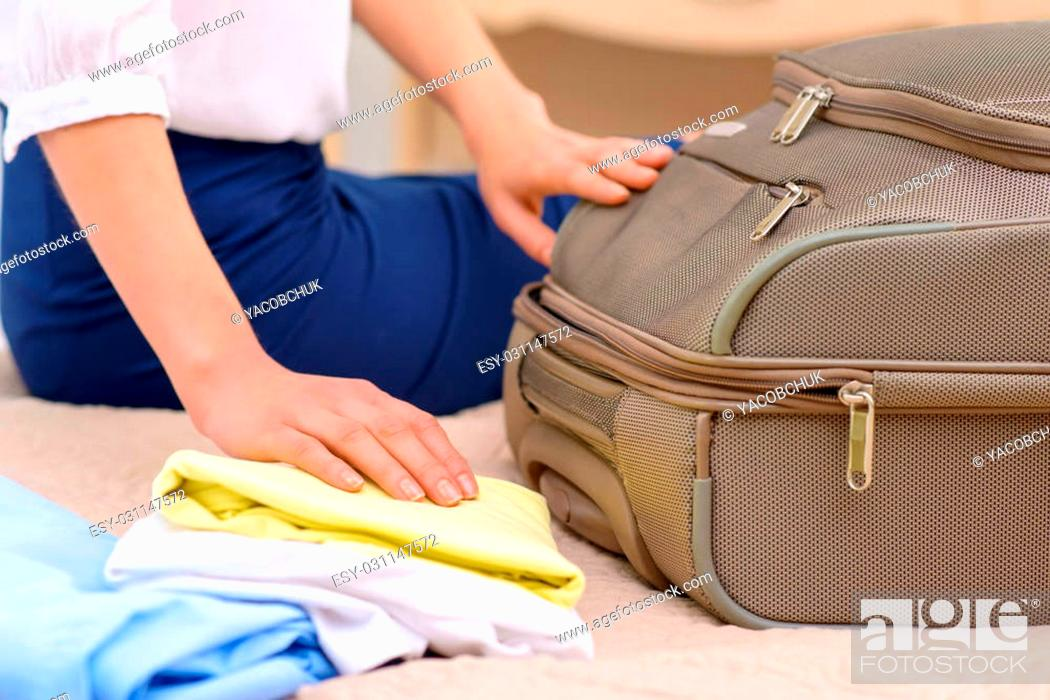 Stock Photo: Unpacking time. Young nice-looking female tourist opens suitcase and starts unpacking.