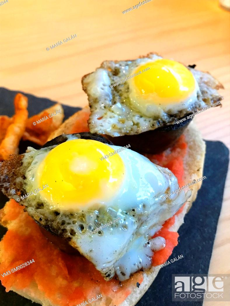 Photo de stock: Spanish tapa: quail eggs with morcilla on toast. Spain.