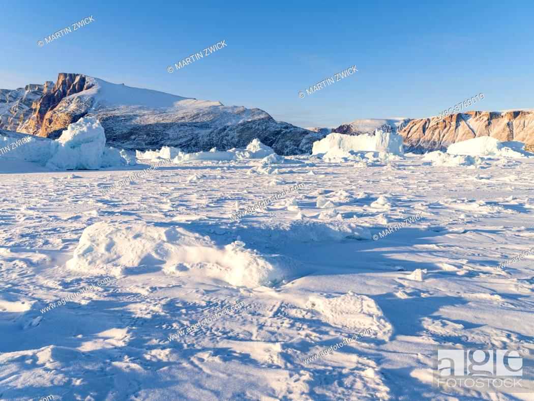 Stock Photo: Icebergs in front of Appat Island, frozen into the sea ice of the Uummannaq fjord system during winter in the the north west of Greenland.