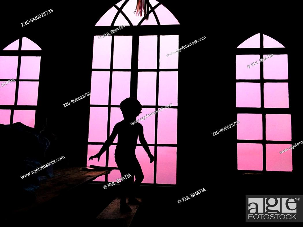 Stock Photo: A young kid standing in a sporting posture in an attic with glass windows, Nova Scotia, Canada.