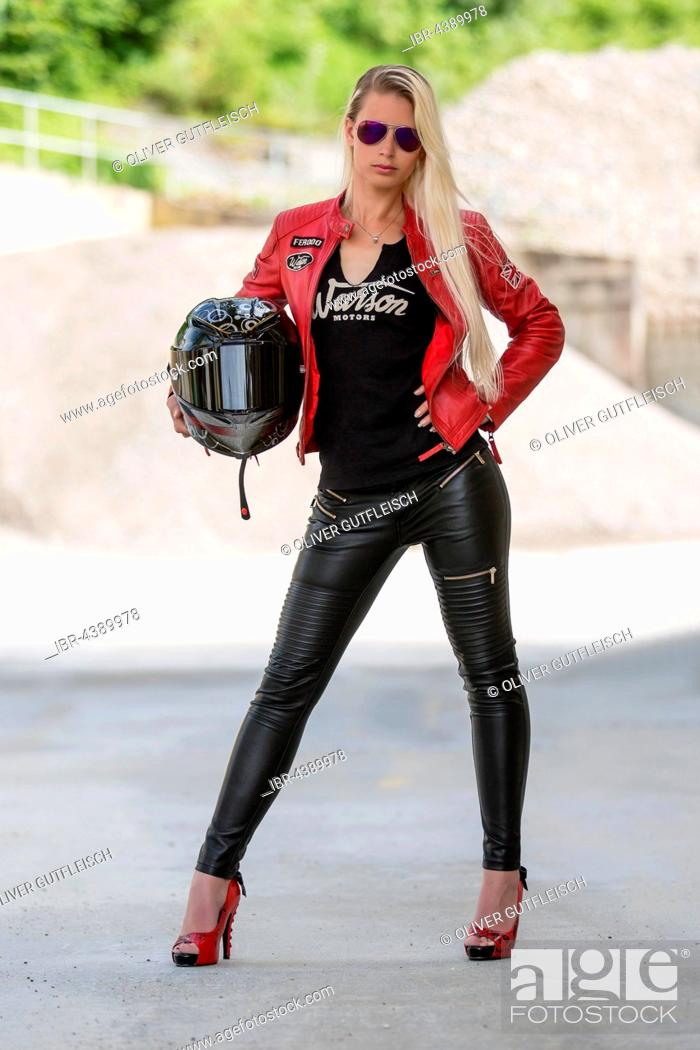 Stock Photo: Young woman with long blonde hair poses posing with motorcycle helmet and sunglasses.