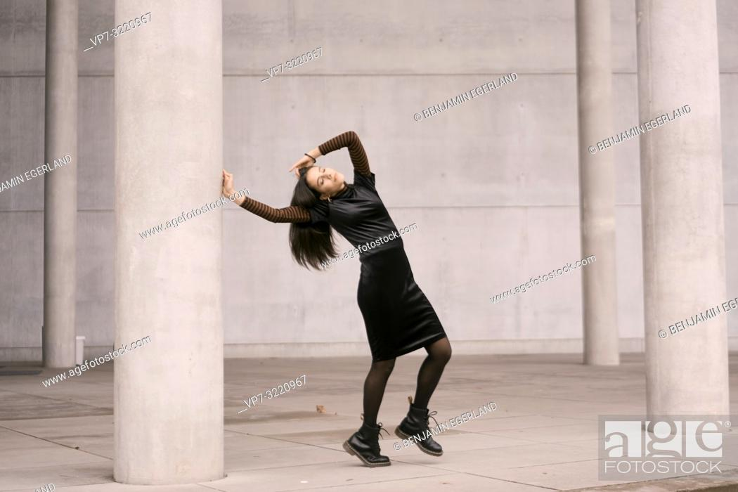 Stock Photo: sensitive emotional woman dancing between tall pillars, architecture, fashionable clothes, in city Munich, Germany.