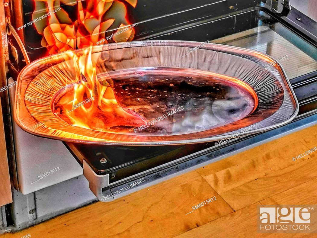 Stock Photo: Ethanol burning on aluminium tray on oven door to make heat in cold kitchen, Stockholm, Sweden, Scandinavia.