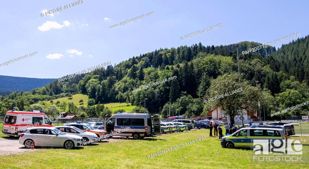 Stock Photo: 12 July 2020, Baden-Wuerttemberg, Oppenau: Police and rescue vehicles are parked at a meeting point near the community in front of a sports home.