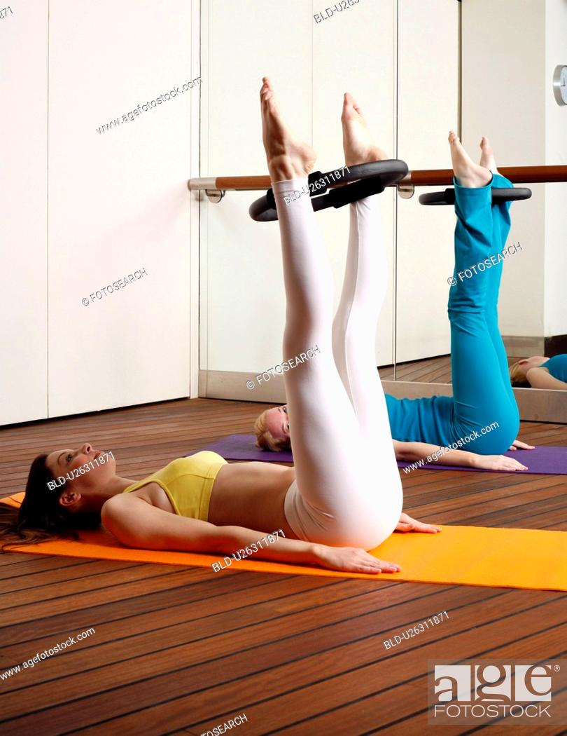 Stock Photo: Two young women performing a pilates exercise.