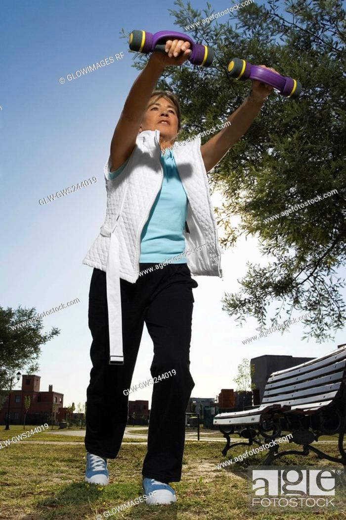 Stock Photo: Low angle view of a senior woman exercising with dumbbells in a park.