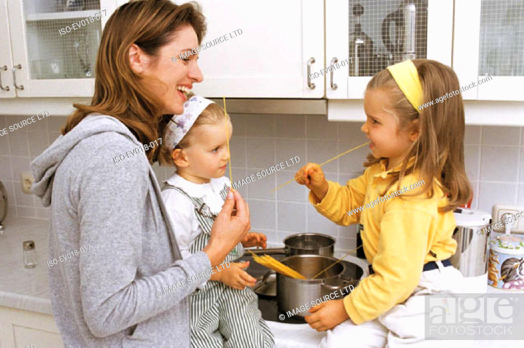 Stock Photo: Mother and daughters in kitchen.