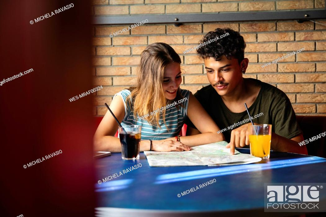 Stock Photo: Smiling young couple sitting at table in a cafe with map.