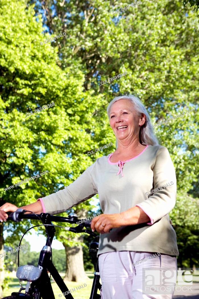 Stock Photo: Mature woman with bike.