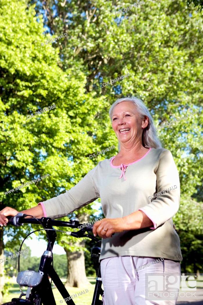 Stock Photo: Mature woman with bike.