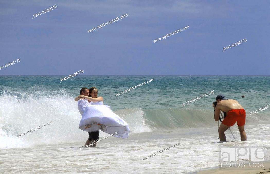 Stock Photo: A bridal couple is photographed by a man in shorts at the sandy beach of Costa Calma on Fuerteventura, Spain, 05 June 2013.